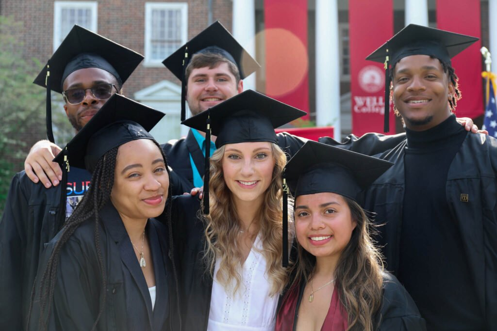 six graduates in their gowns standing together